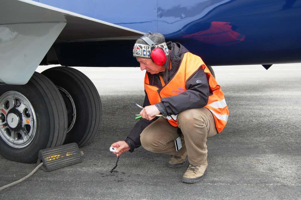 MOOK I AKSJON: Her måler Reinhard Mook temperaturen på flyhjulet og den frosne rullebanen etter landing. Foto: PRIVAT
